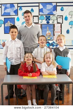 Portrait Of Group Of Primary Schoolchildren And Teacher Sitting At Desk In Classroom