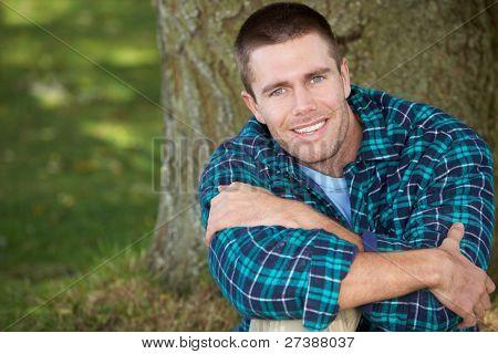 Man sitting against tree trunk