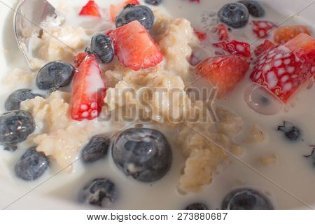 Oatmeal With Milk, Strawberries, & Blueberries In A White Bowl With A Spoon.
