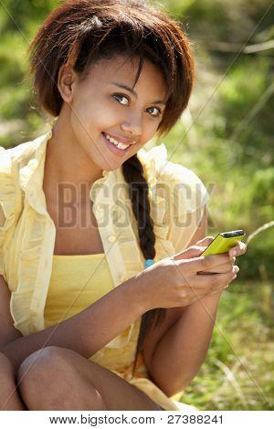 Teenage girl using phone outdoors