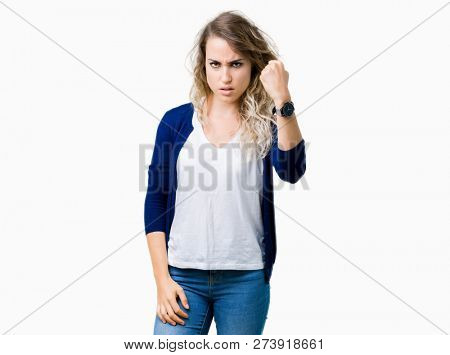 Beautiful young blonde woman over isolated background angry and mad raising fist frustrated and furious while shouting with anger. Rage and aggressive concept.
