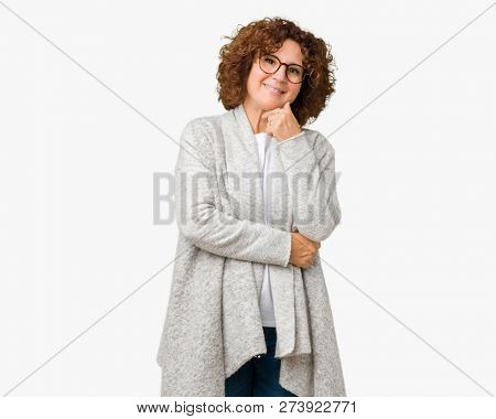 Beautiful middle ager senior woman wearing jacket and glasses over isolated background looking confident at the camera with smile with crossed arms and hand raised on chin. Thinking positive.