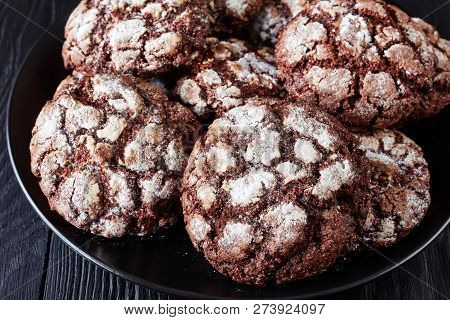 close-up of Chocolate Crinkle cookies. Cracked chocolate biscuits. Chocolate biscuits, Christmas cookies on a black plate on a black wooden table, view from above poster