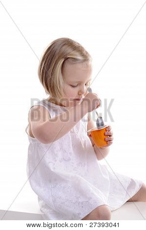 Little Girl Eating Yogurt. Isolated On White