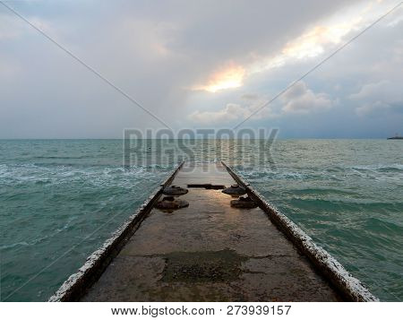 Concrete Wet Buna With A Reflection Of Sunlight On A Wet Surface In Turquoise Water Under A Sky With