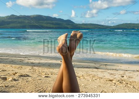 Traveler Girl In Vacation Relaxing On The Beach. Young Girl In Vacation. Close Up Of Girls Legs On T