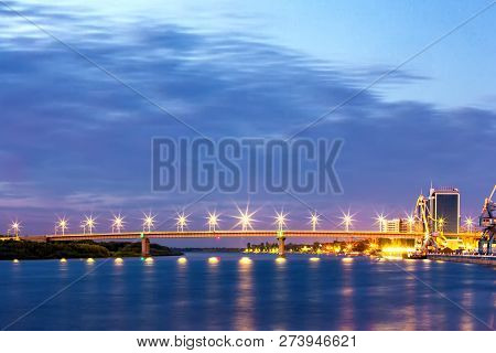 Road Concrete Bridge On Supports Across The Volga River, Lampposts Illuminate At Dusk At Night, Gree