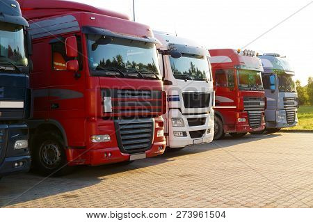 Several Trucks Lined Up In A Row On A Parking Lot.