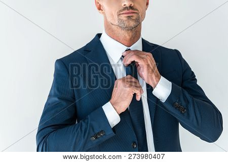 Cropped Image Of Businessman Tying Tie Isolated On White