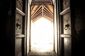 Opened old ancient temple door gate with radiance light with effect of light at the end of the tunnel poster