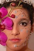 Girl wearing makeup made of rhinestone flowers with a pink orchid poster
