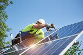 Technician connecting solar photo voltaic panel to metal platform using screwdriver standing on ladder on bright blue sky copy space background. Stand-alone solar panel system installation concept. poster