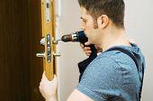 Young handyman in uniform changing door lock. poster