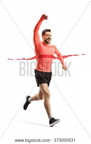 Full length shot of a young man running a race on the finish line and gesturing win isolated on white background