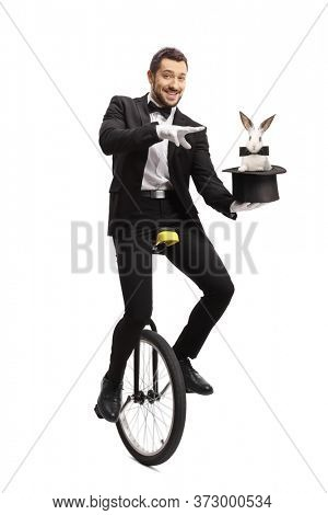 Magician on a unicycle and performing a magic trick with a hat and a rabbit isolated on white background