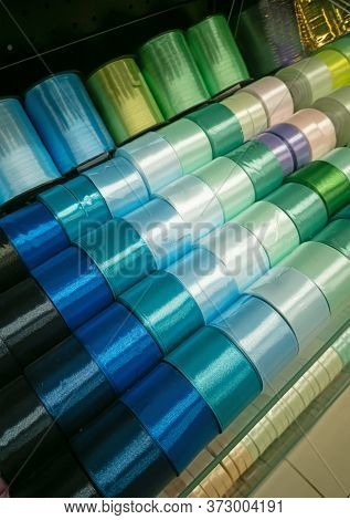 Shiny Silk Ribbons On A Shelf In Store. Homemade Concept. Multicolored Ribbons In Fabric Store And