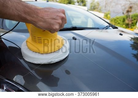 Male auto service staff cleaning a car bonnet with rotating wash brush