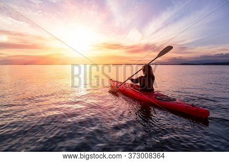 Sea Kayaking In Calm Waters During A Colorful And Vibrant Sunset. Adventure Girl In Red Kayak. Locat