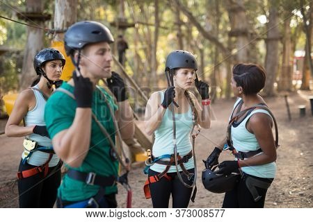 Coach and trainee wearing protective helmet in forest