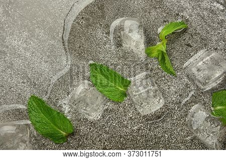 Several Ice Cubes And Fresh Green Mint Leaves On Gray Table Surface, Elevated Top View, Directly Abo
