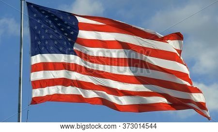 American Flag And Sky With Cloudy Clouds. Closeup Of Large American Flag Waving In Front Of Blue Sky