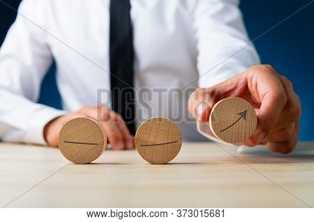 Businessman Assembling An Arrow Pointing Upwards With Wooden Cut Circles In A Conceptual Image Of Bu