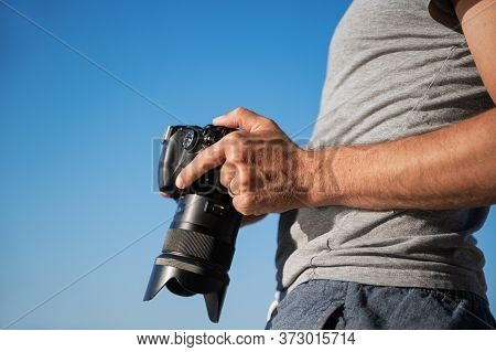Closeup View Of Male Photographer Checking Settings On His Camera Screen Standing Outside Under Clea