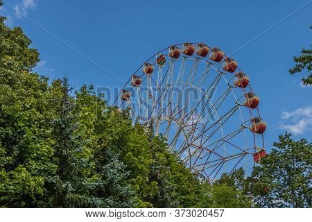 Ferris Wheel And Summer Colors. A Ferris Wheel In The Dance Past Some Trees.