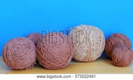Skeins Of Brown Woolen Threads On A Blue Background Close-up