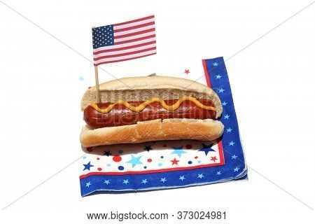 Hot Dog. Hot Dog with mustard and an American Flag on a Festive star pattern napkin. Isolated on white. Room for text.