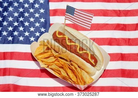 Hot Dog. Hot Dog with Potato Chips and an American Flag on an American Flag place mat. Hot Dogs are enjoyed World Wide by hungry people.