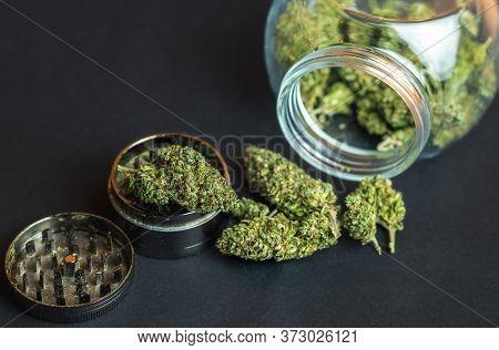 Medical Marijuana Flower Buds In Glass Jar And Grinder On Dark Backdrop