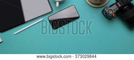 Creative Worktable With Smartphone, Tablet, Stylus, Camera, Decoration And Copy Space