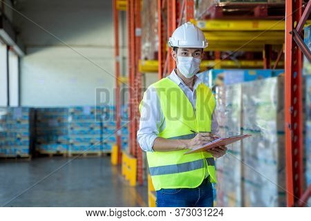 Worker Working Wearing Protective Mask To Protect Against Covid-19 Working And Checking Product In A