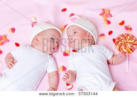 Newborn twin babies lying among sweets