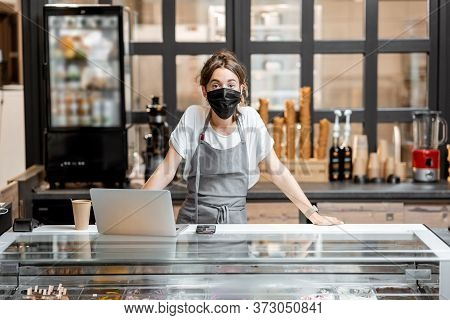 Portrait Of A Saleswoman Or Small Business Owner Wearing Medical Mask At The Counter In Cafe Or Smal