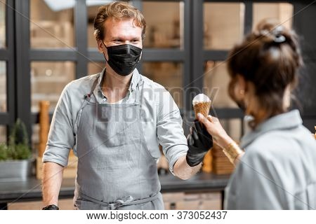 Salesman In Protective Mask Selling Ice Cream For A Young Client In The Shop. Concept Of New Social