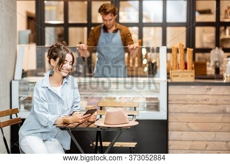 Young Female Customer Sitting With Phone At The Cafe Or Pastry Shop With A Seller On The Background