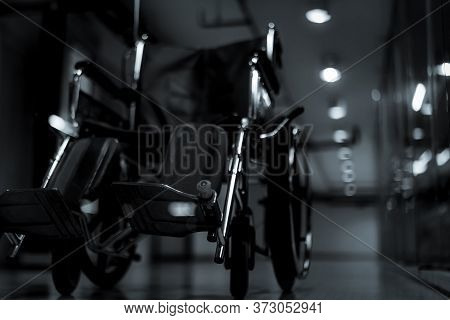 Blurred Empty Wheelchair At Hallway In Hospital At Night For Service Patient And Disabled People. Me
