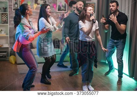 Cheerful Young Woman Singing On Microphone While Her Friends Are Dancing At The Party.