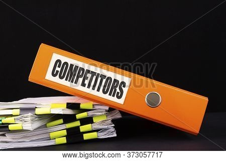 The Office Folder With The Inscription Competitors Lies On The Table With A Stack Of Documents.