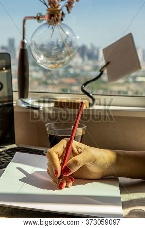 Hand Of Business Woman Writing On Paper At Her Workstation. Business Concept.