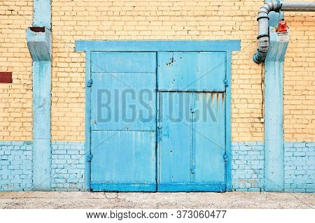 Cityscape. Urban Symmetric View Of Abandoned Factory Building Blue Painted Rusty Gate On Yellow Bric