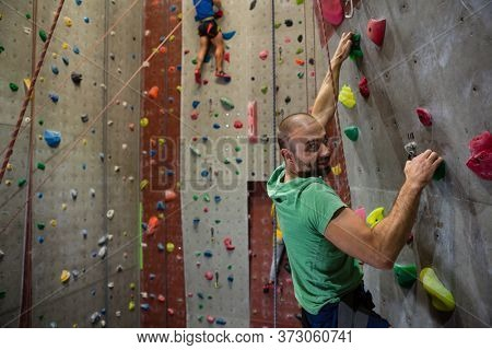 Portrait of smiling male athlete climbing wall in health club