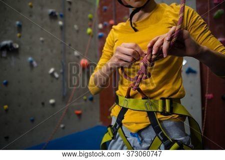 Midsection of female athlete tying rope while standing in health club