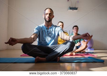 Male instructor with students meditating in health club