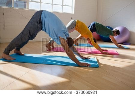 Male instructor with students practicing downward facing dog pose in yoga studio