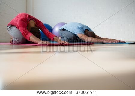 Instructor with female student practicing child pose in yoga studio
