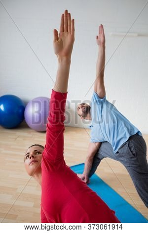 Male Instructor with female student practicing triange pose in health club