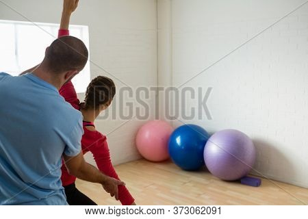 Rear view of male instructor assisting student in exercising at yoga studio